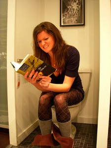 girl sitting on toilet reading