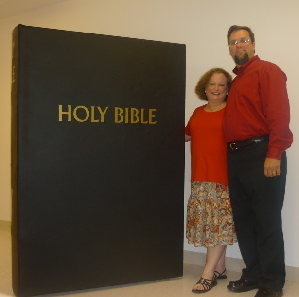 big bible with people standing beside