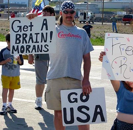 get a brain morans guy holding mispelled sign