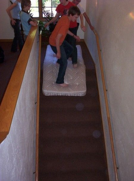 kids riding mattress down stairs