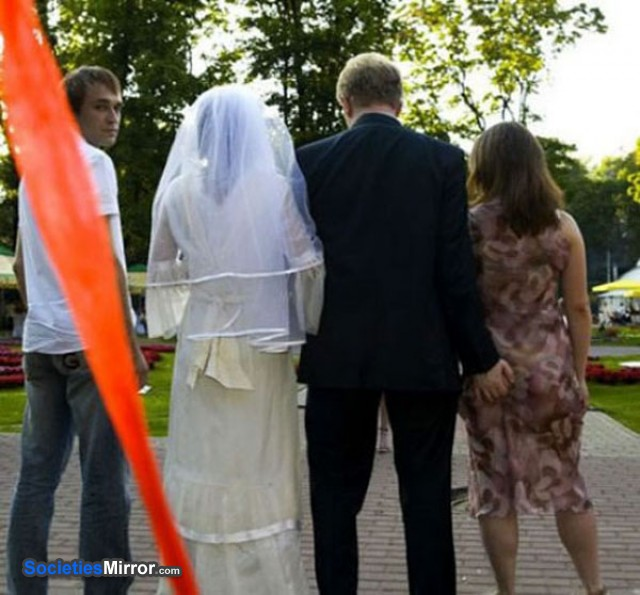 groom walking with bride has one hand on another woman's bum
