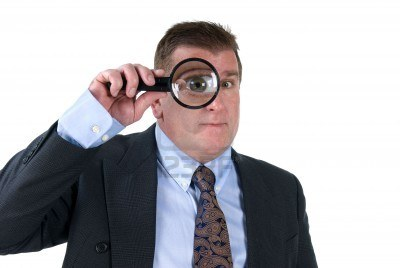 man with magnifying glass over eye