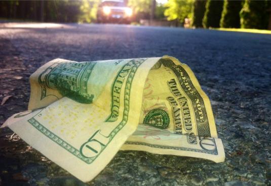 ten dollar-bill laying on street